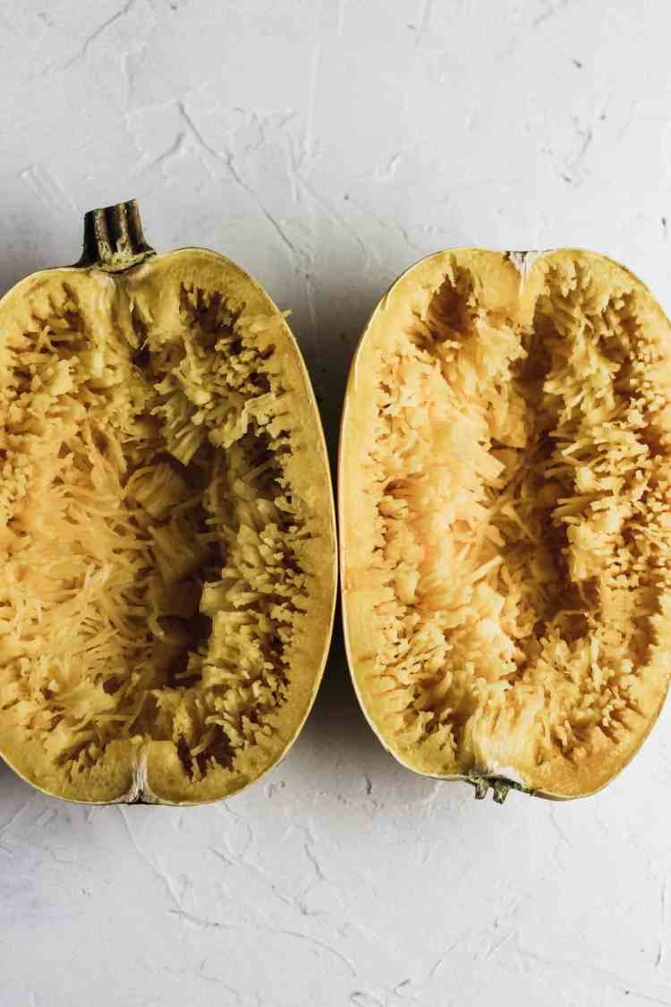 Halved cooked spaghetti squash with spaghetti strands pulled out with a fork.