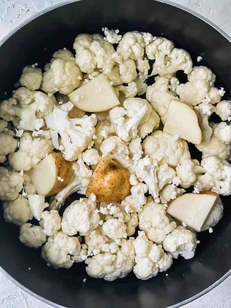 Cauliflower florets and cubed potato covered with water in a stock pot.