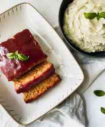 Healthy Chicken Meatloaf sliced on a white dish with garlic cauliflower mashed potatoes on the side.