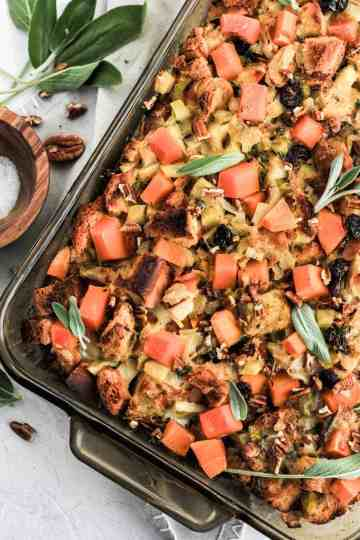 Butternut squash stuffing in a glass baking dish with leaves of sage and a wooden bowl with salt.
