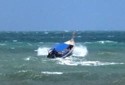 longtail boat on high waves