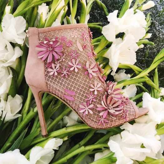 Dimensional flower appliqués bloom across the fishnet mesh of a peep-toe bootie set on a slim stiletto