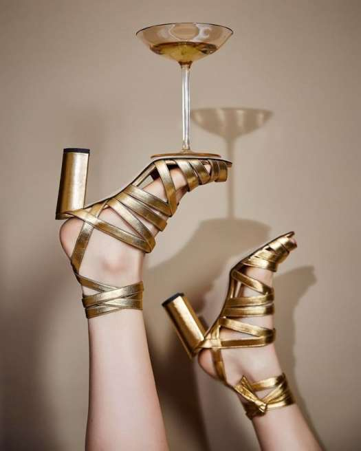 Shimmery golden leather illuminates a gorgeously strappy Italian sandal lifted by a tall, slender heel