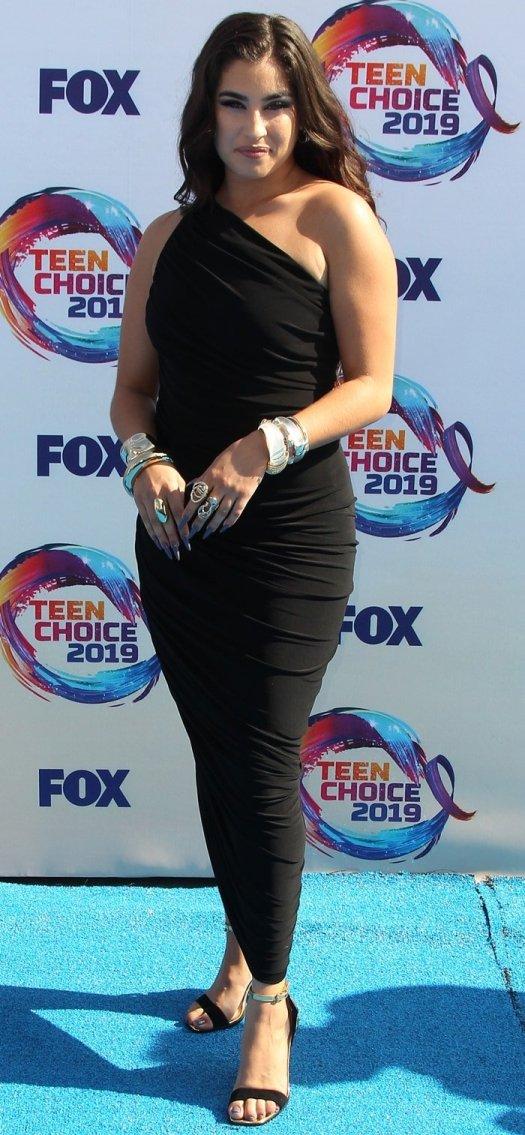 Lauren Jauregui's Norma Kamali dress featuring a sleeveless design, an asymmetric hem and a mid-length