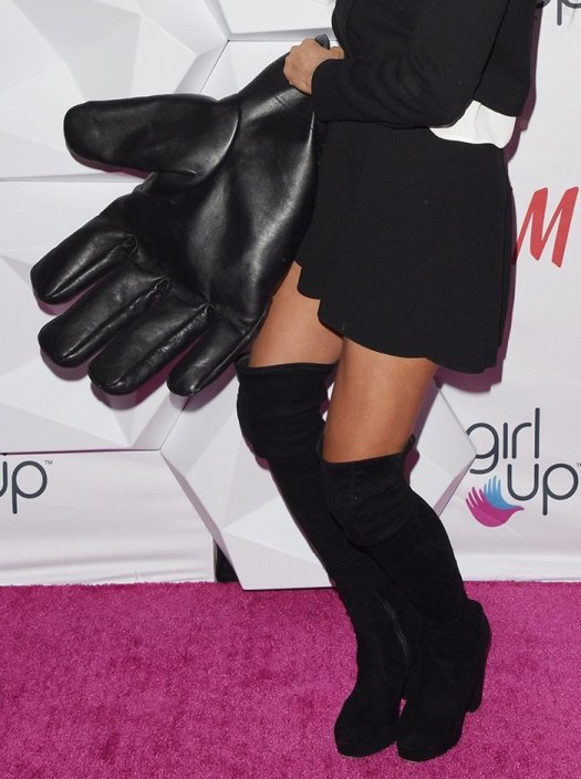 Jameela Jamil tops off her look with a huge glove-shaped leather bag and thigh-high boots