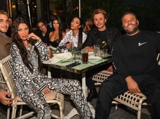 LIV nightclub owner David Grutman smiling with Bella Hadid, Kourtney Kardashian, Jonathan Foodgod Cheban, and Bad Bunny are seen at Swan