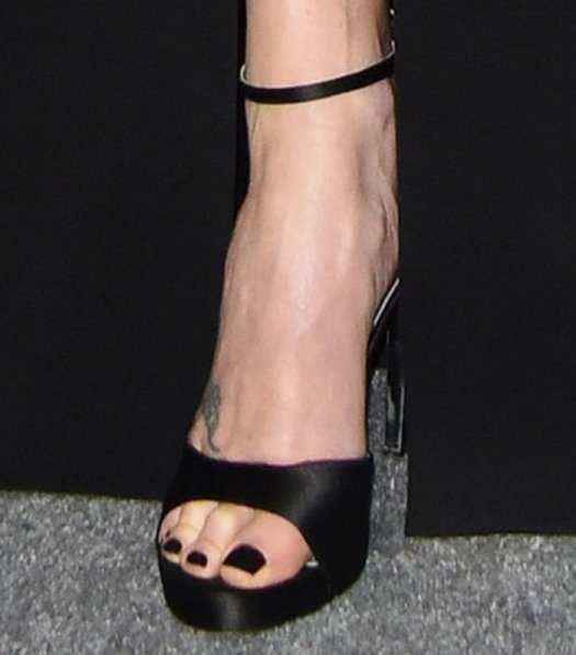 Charlize Theron shows off her foot tattoo in black heels