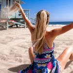 donna in spiaggia che solleva la sabbia