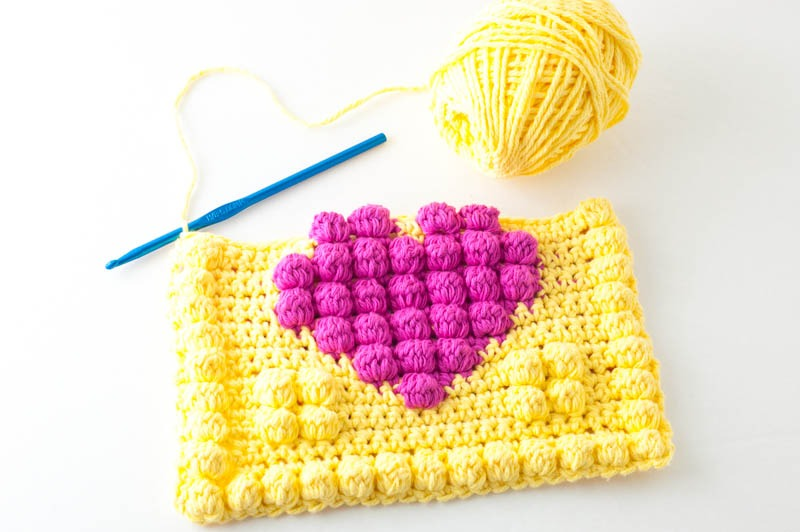 In-progress view of the front side of the bobble heart potholder, including a blue crochet hook and skein of yellow yarn