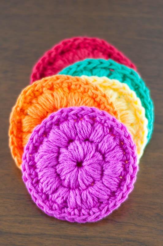 five brightly colored crochet face scrubbies