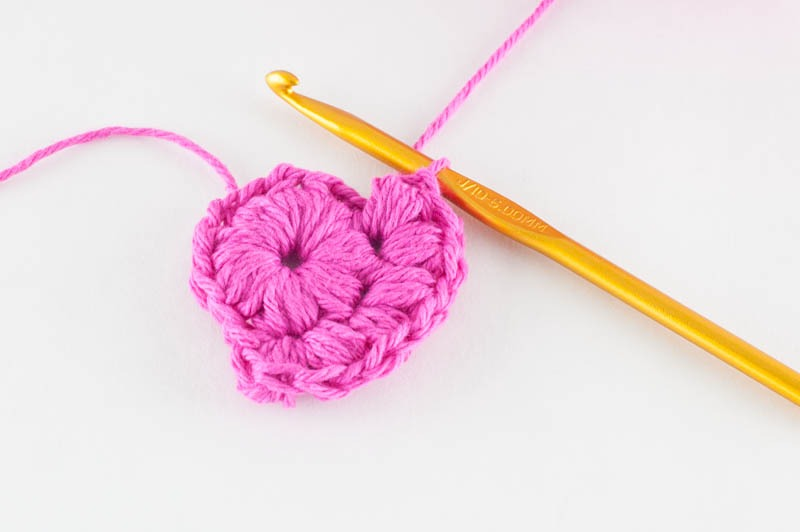 in-progress photo of the second round of the cotton face scrubbies, pink yarn and a gold crochet hook