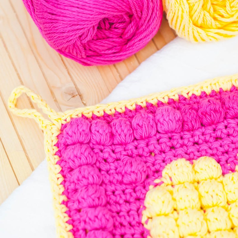 close-up view of two pink and yellow balls of yarn and a bobble heart potholder on a white towel and wooden background