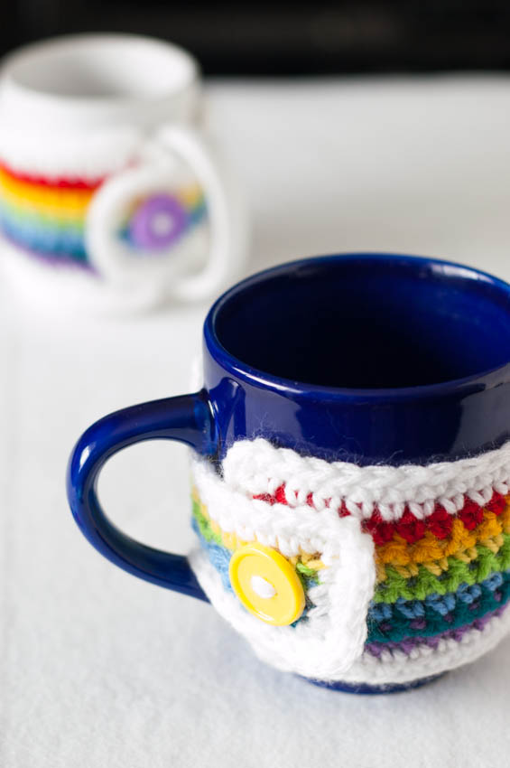 Brighten up your morning coffee and celebrate spring with a crocheted rainbow mug cozy! This free crochet pattern features a video and step-by-step photo-tutorial. #youshouldcraft #freecrochetpattern #rainbow #crochetmugcozy
