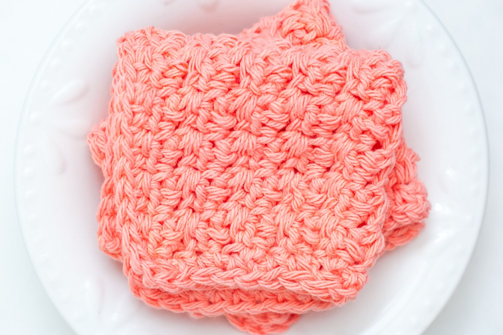 Two coral-colored crochet dishcloths in a white bowl