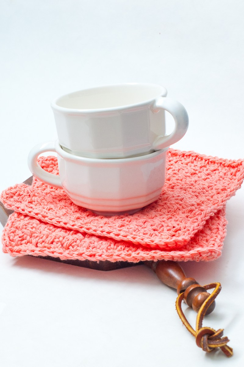Two white mugs and two coral crochet dishcloths on a wooden handle