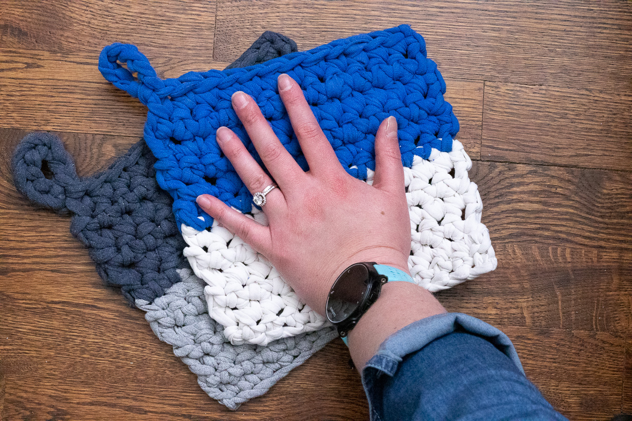 two crocheted potholders with a hand on top