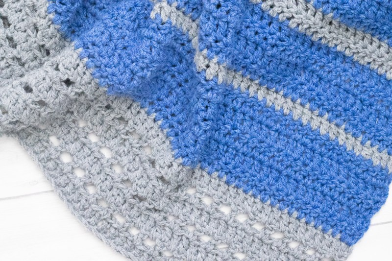 horizontal image of a blue and grey crocheted blanket on a white background