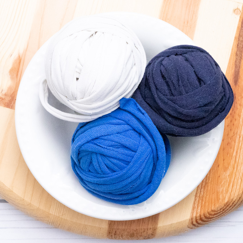 white bowl on a round wooden cutting board with three balls of t-shirt yarn in blue, white, and navy