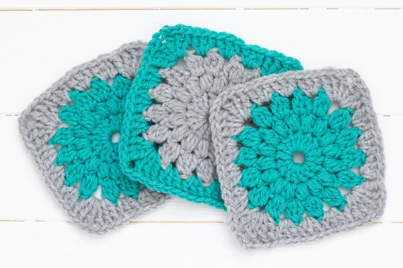 three grey and teal sunburst granny squares spread out on a white wood background