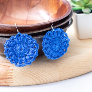 blue crocheted earrings hanging on wooden bowls