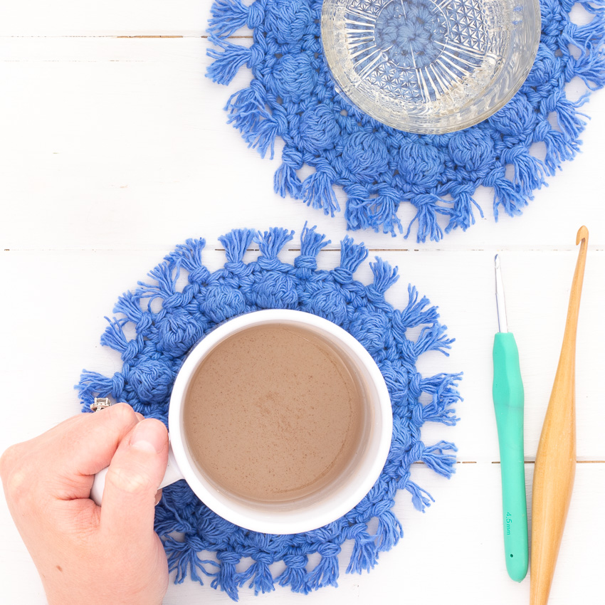 hand holding a white mug on crocheted bobble coasters, with crochet hooks on the side