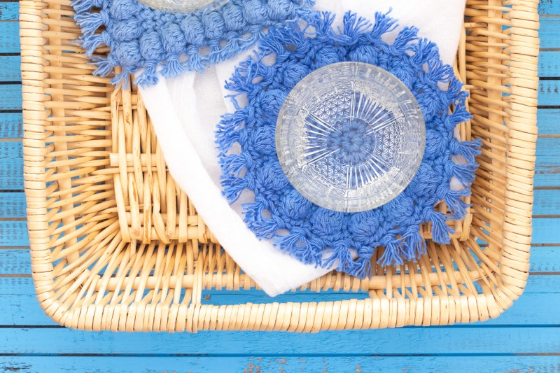 rectangular basket with white towel and two crocheted boho bobble coasters
