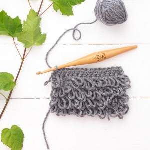grey swatch of loop stitch crochet with a hook, yarn ball, and leaves on a white wooden background