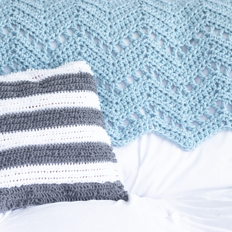 white couch with blue crocheted blanket and grey and white striped loop stitch pillow
