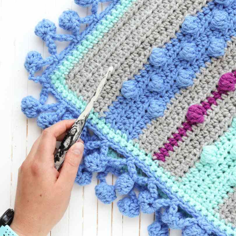 corner of bobble stripe blanket with hand and crochet hook