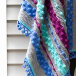 hanging crocheted bobble blanket with stripes of blue, grey, and purple
