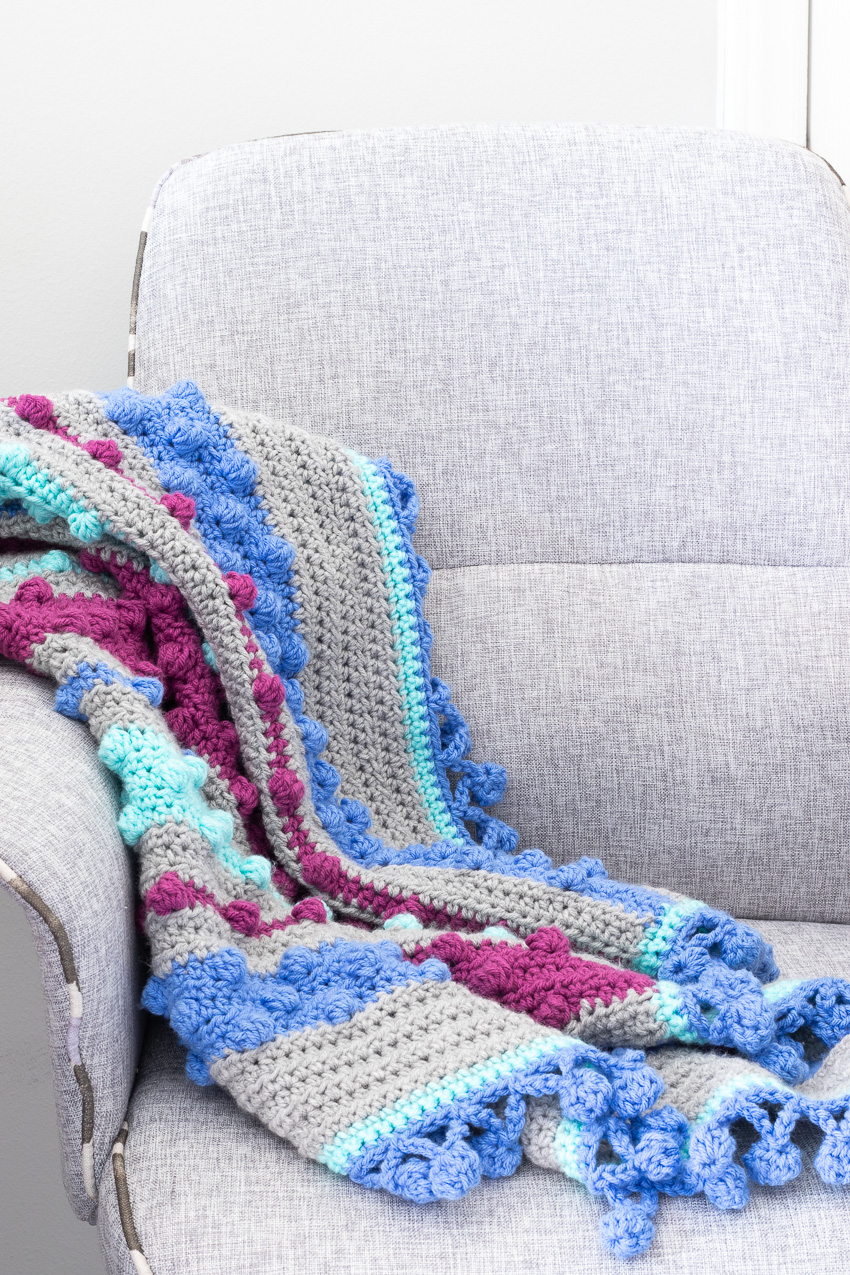 grey office chair with a crocheted bobble stripes blanket over the arm