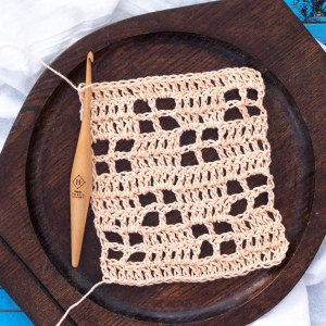 dark wooden tray with a caramel colored crochet swatch and wooden hook