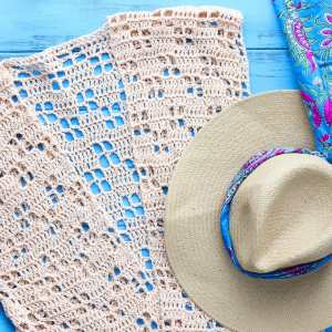 cream crocheted cardigan and a straw hat on a blue background