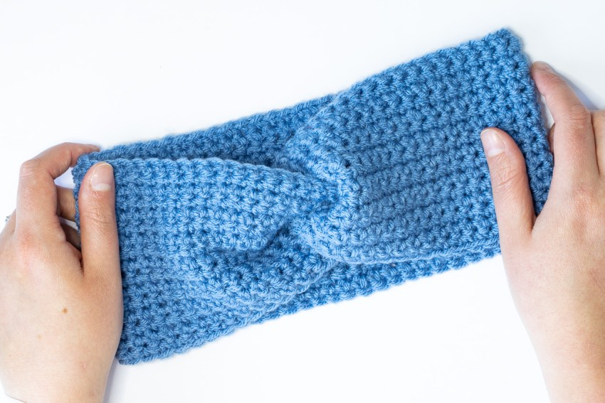 two hands holding a blue twisted ear warmer