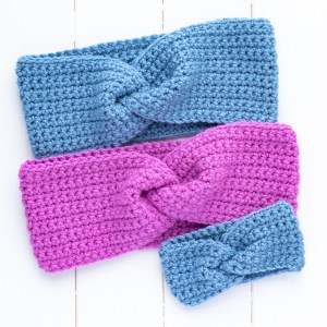 three crochet twisted ear warmers on a white wooden background