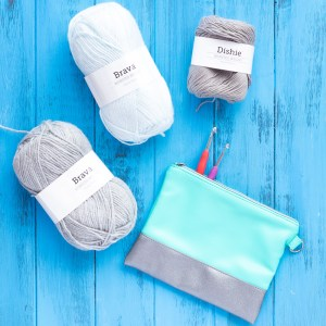 three balls of yarn, two crochet hooks, and a turquoise pouch on a blue wooden background