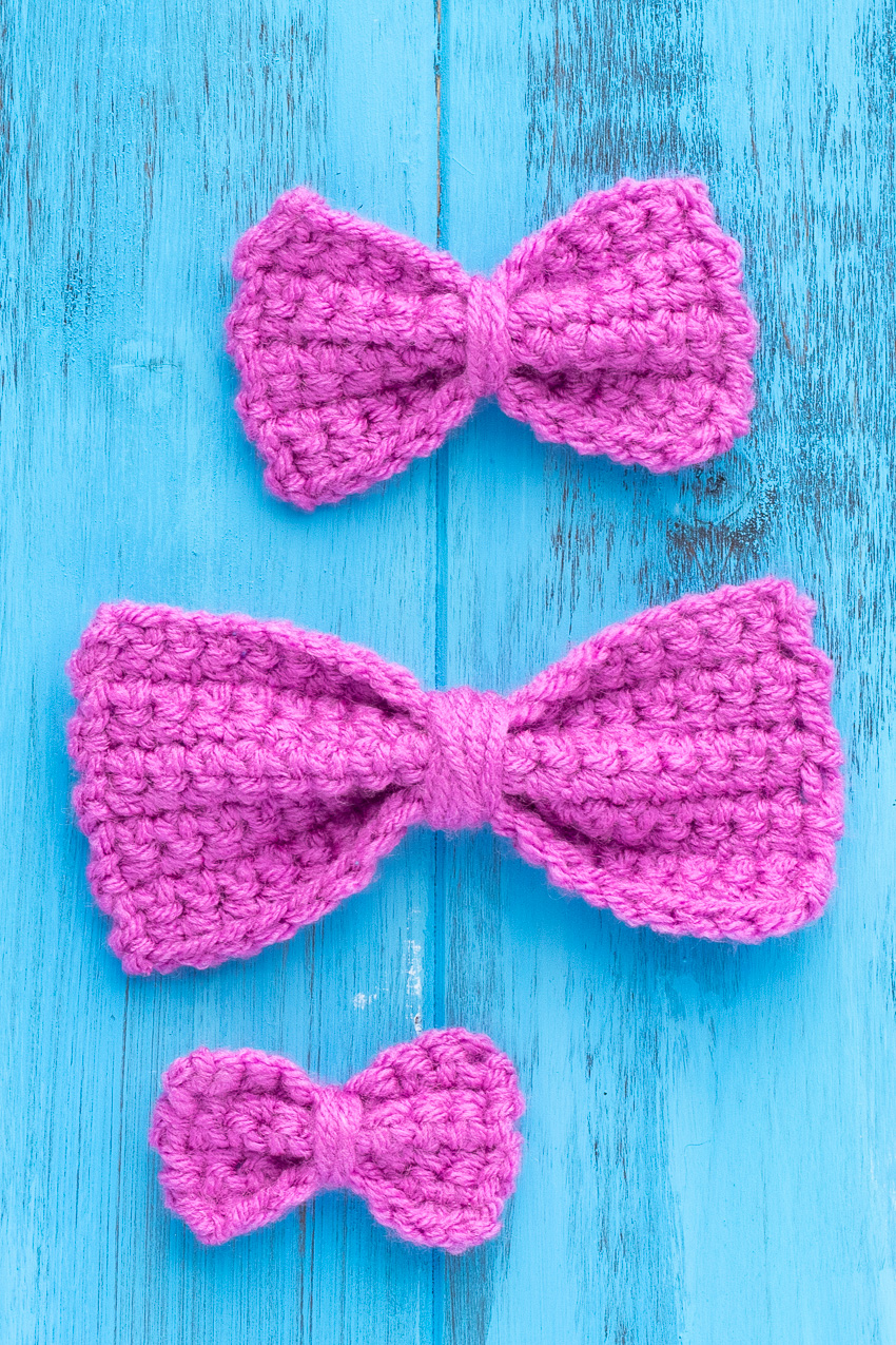 three bright purple crocheted bows on a blue wooden background