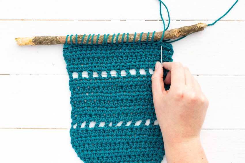 teal crocheted wall hanging on a stick, hand pulling a tapestry needle