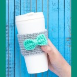 """hand holding a white cup with a crocheted coffee sleeve with bow and text """"beginner coffee sleeve - you should craft"""""""