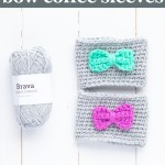 """two coffee sleeves with bows and a small skein of grey brava yarn with text """"how to crochet bow coffee sleeves - beginner crochet pattern from you should craft"""""""