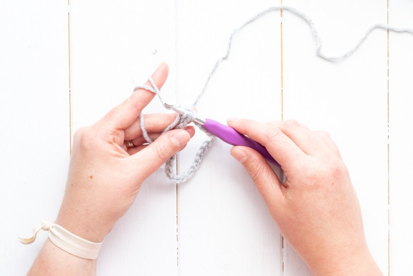two hands joining a crocheted chain with a slip stitch