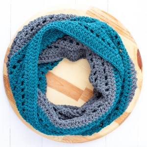 teal and dark grey color-blocked infinity scarf on a wooden circle