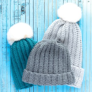 three crocheted beginner ribbed hats on a blue wooden background