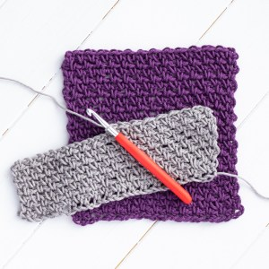 purple dishcloth with a grey in-progress linen stitch swatch and red crochet hook