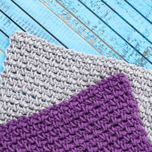 purple and grey linen stitch dishcloths on a blue wooden background