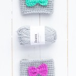 vertical image depicting two coffee sleeves with bows and a small skein of grey brava yarn
