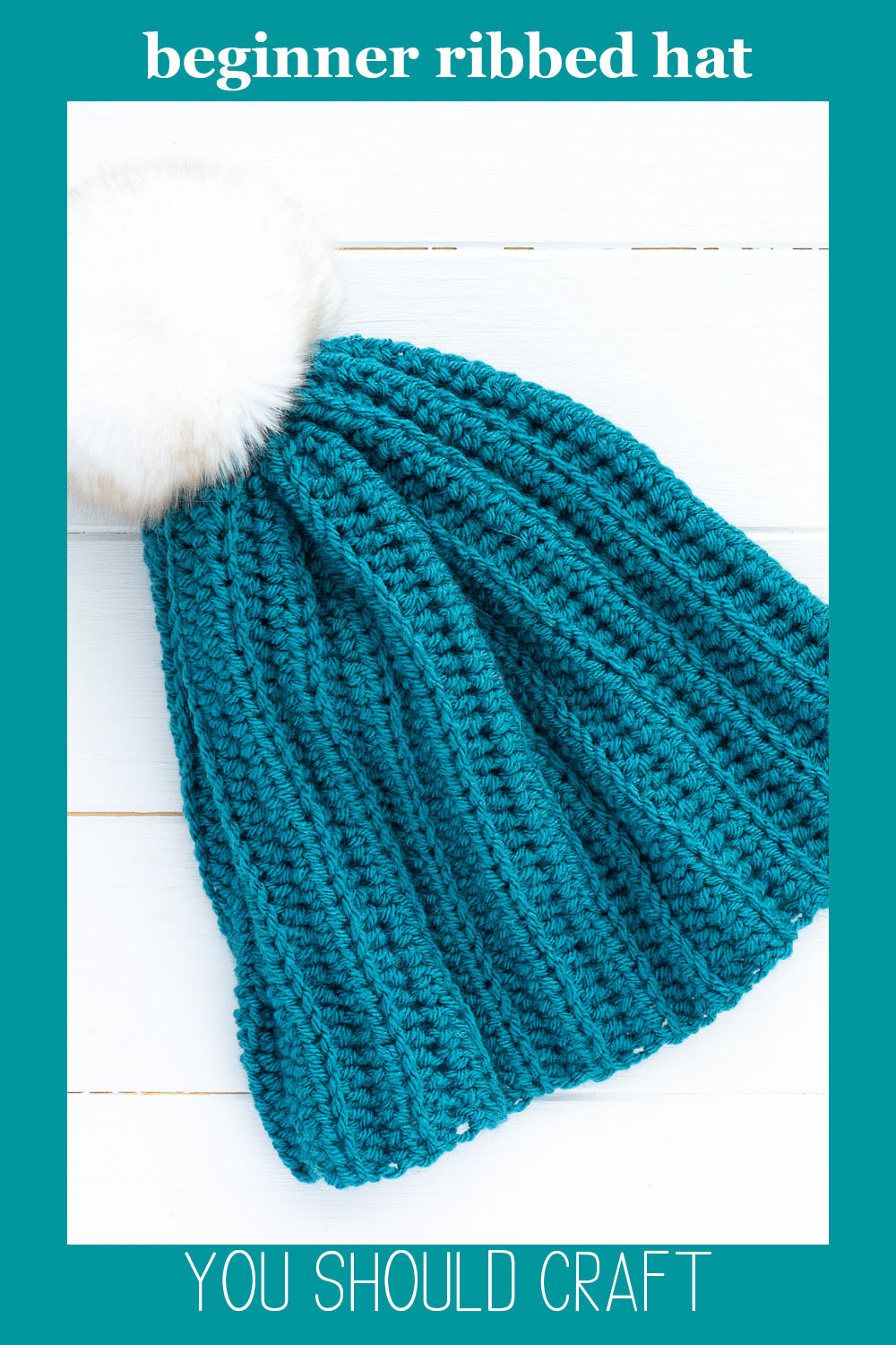 """ribbed beanie crocheted with teal yarn with a white fur pom and text overlay """"beginner ribbed hat - you should craft"""""""