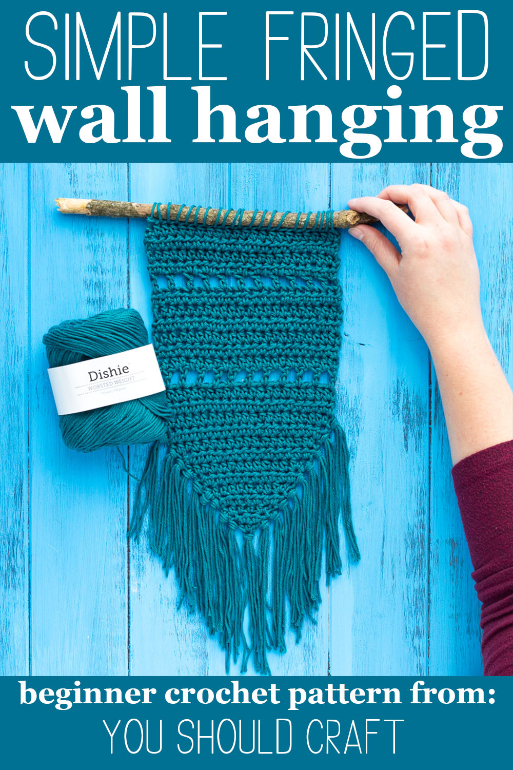 "hand holding up a teal crocheted wall hanging, next to a ball of Dishie cotton yarn with text ""simple fringed wall hanging - beginner crochet pattern from you should craft"""