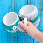 hand holding two mugs with crocheted striped mug cozies on a blue wooden background