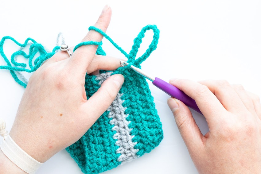two hands crocheting the loop on the striped mug cozy